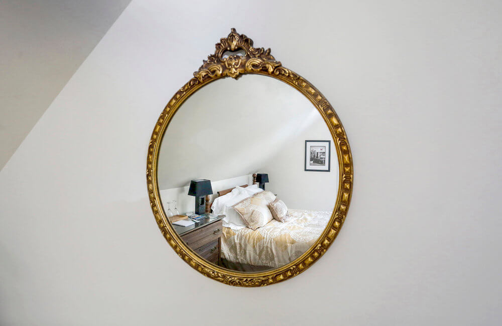 Architectural Photography interior of a mirror reflects a bed at a Freeport Bed and Breakfast