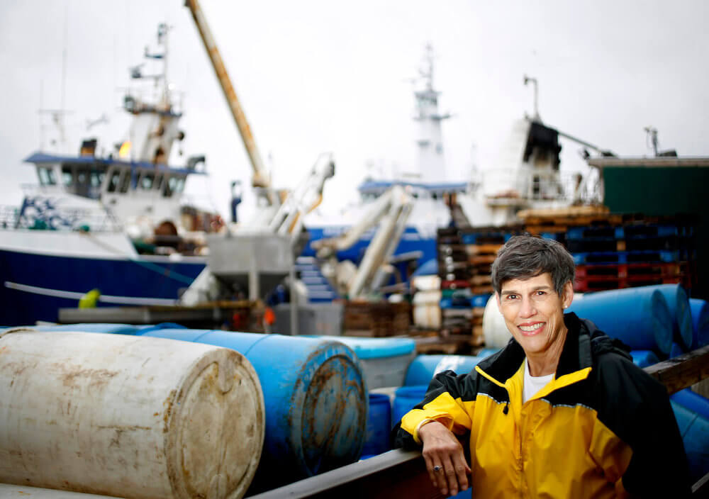Portrait photography of Emily Lane, vice president of sales at Calendar Islands Maine Lobster, near docked fishing boats along the Portland waterfront