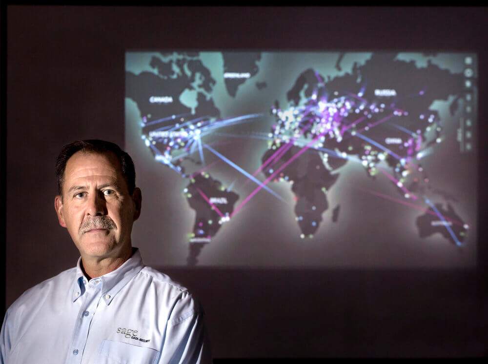 Portrait photography of Rick Simonds, Sage Data Security COO, near a screen with real-time cyber threats in the world at Sage Data Security in Portland