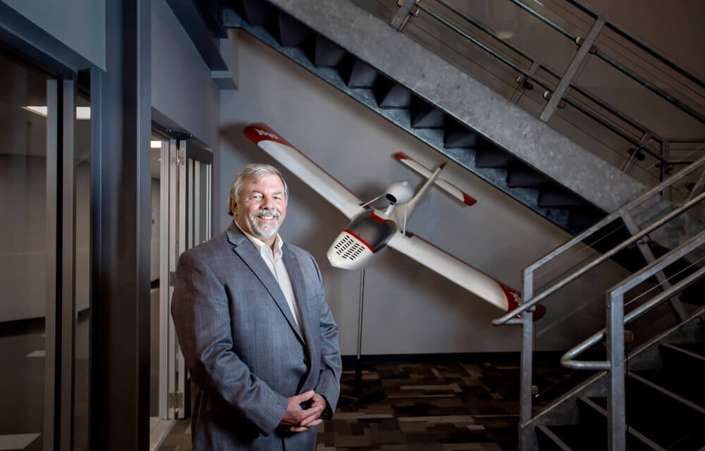 Portrait photography of Steve Levesque, executive director of the Midcoast Regional Redevelopment Authority, in the TechPlace lobby near a scale model of an Atol 650, an amphibious aircraft being built by Atol USA, at Brunswick Landing in Brunswick