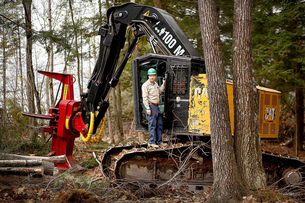 Portrait photography of Tom Cushman, owner of Maine Custom Woodlands, on a feller buncher in the woods in Gray Maine