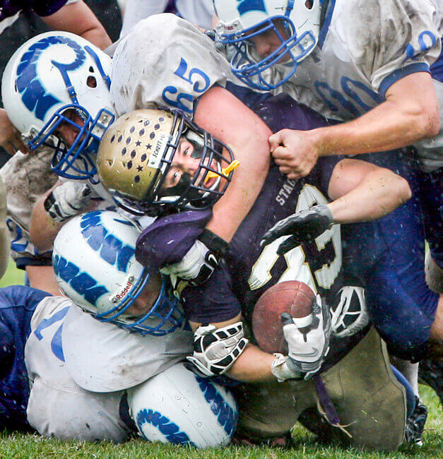 Maine photography of a high schoolfootball player being tackled by many players at a event