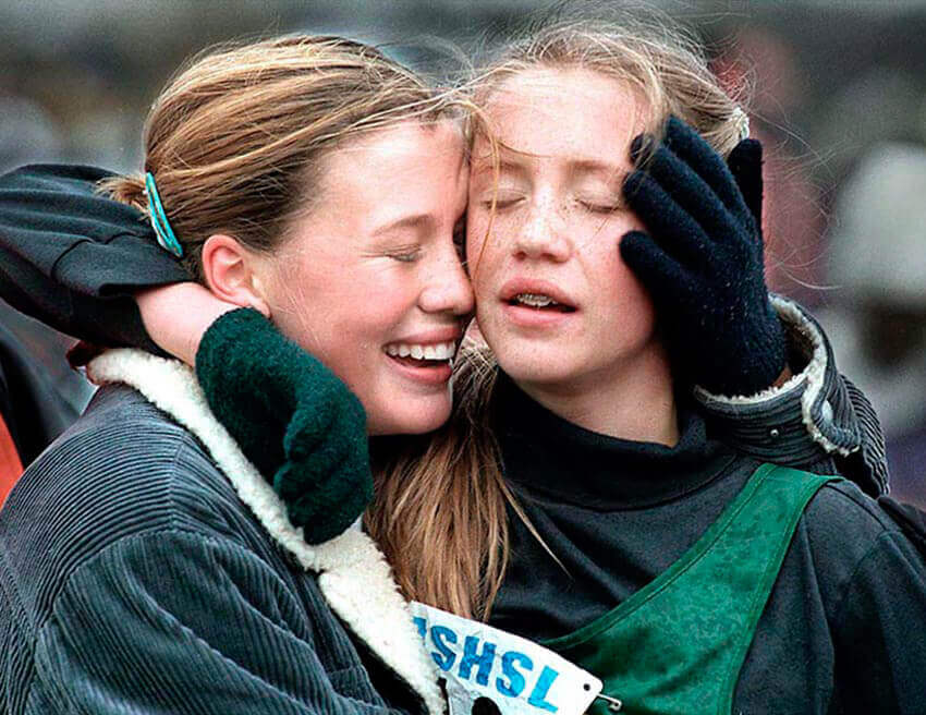 Photography of of two high school girls embracing after a cross country race in Minnesota