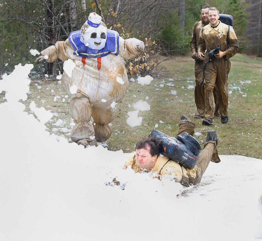 Maine photography of people dressed up like characters from the movie Ghostbusters cross the finish line at an event in Maine
