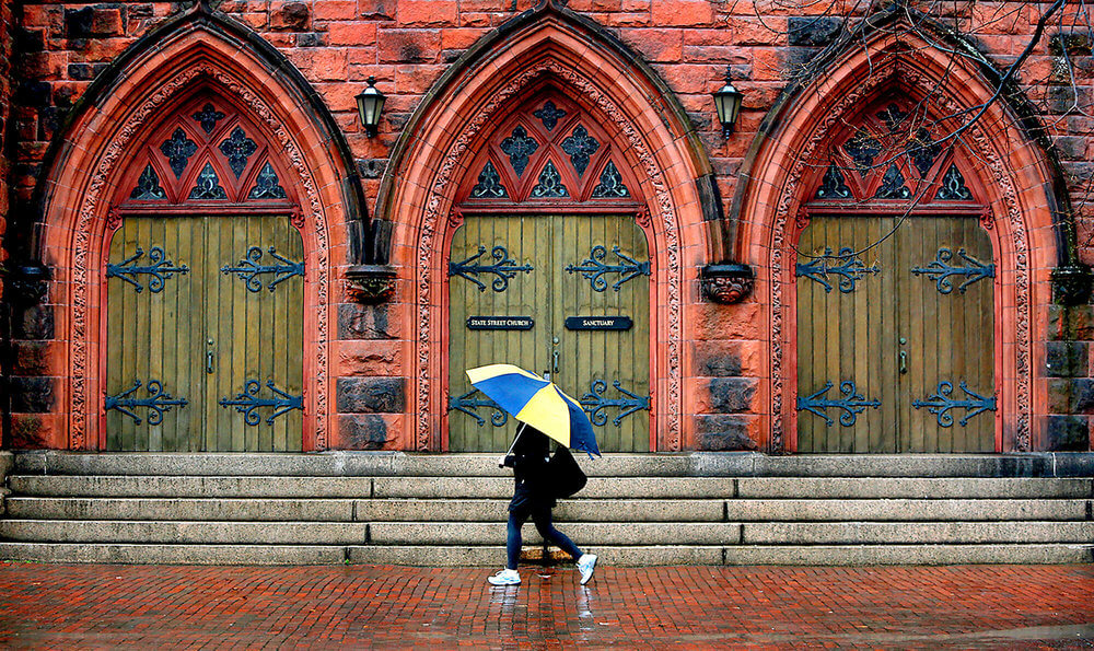Maine photography of a woman walking past a red church in Portland Maine