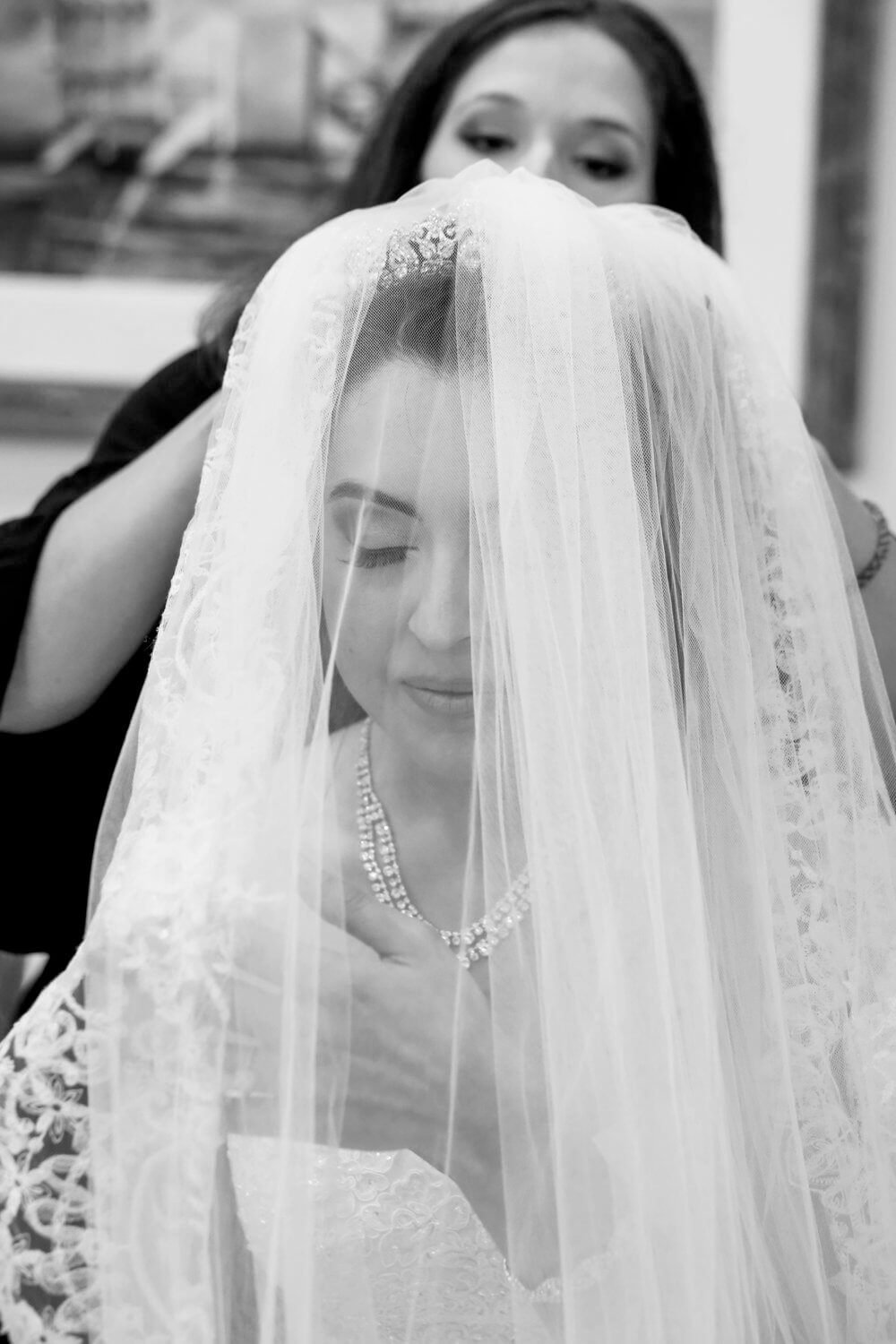Black and white wedding photography of a bride's face shown through a veil in Maine