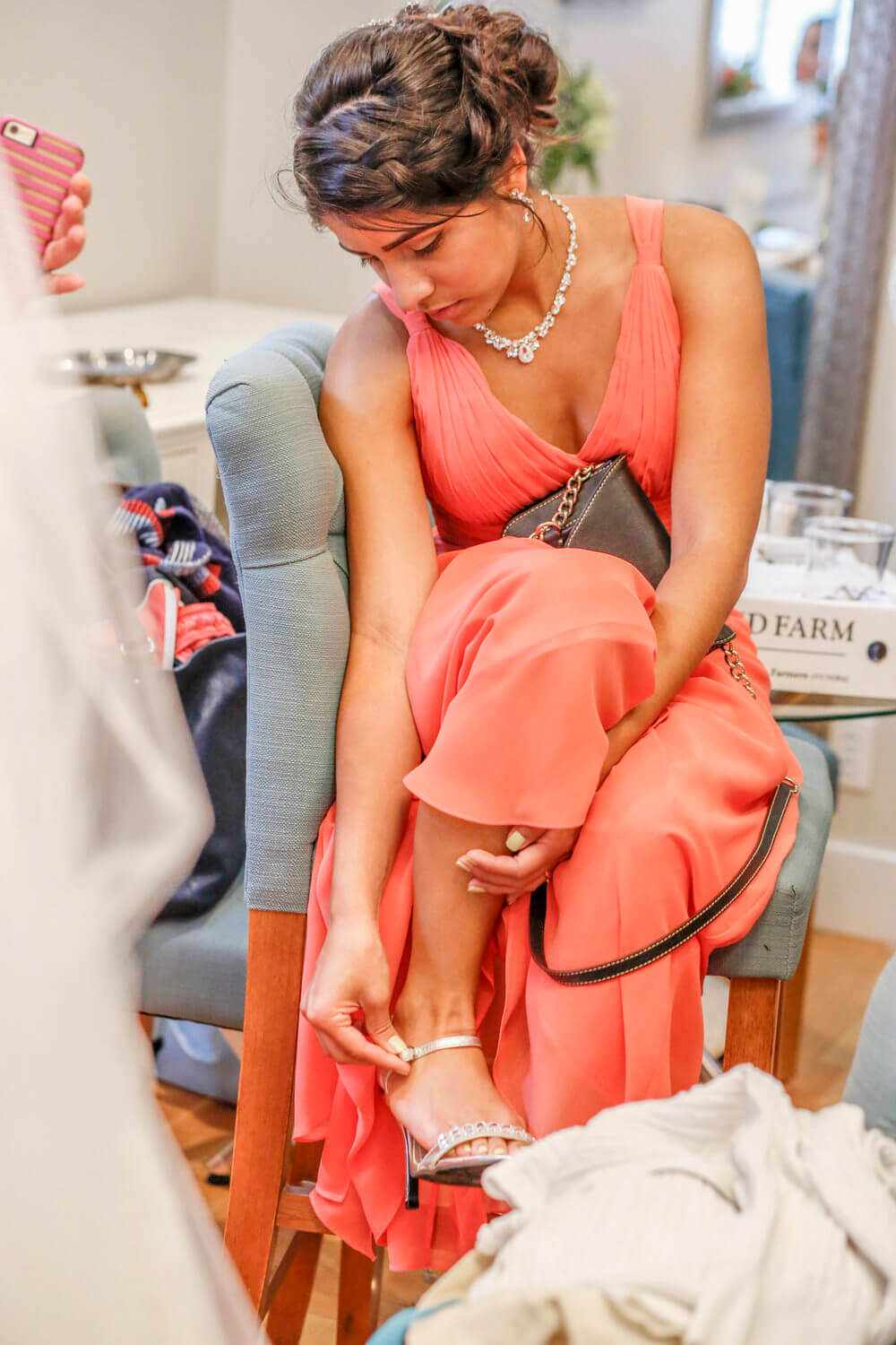 Wedding photography of bridesmaid putting on her shoes in the hotel in Maine