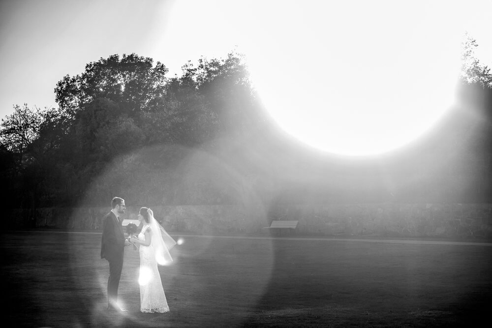 Wedding photography of a black and whit image with the sun glare circling the couple at Portland Head Light House