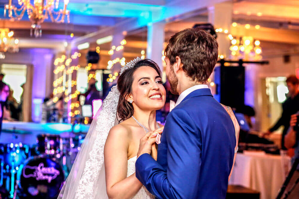 Wedding photography of a bride smiling at her husband during their first dance