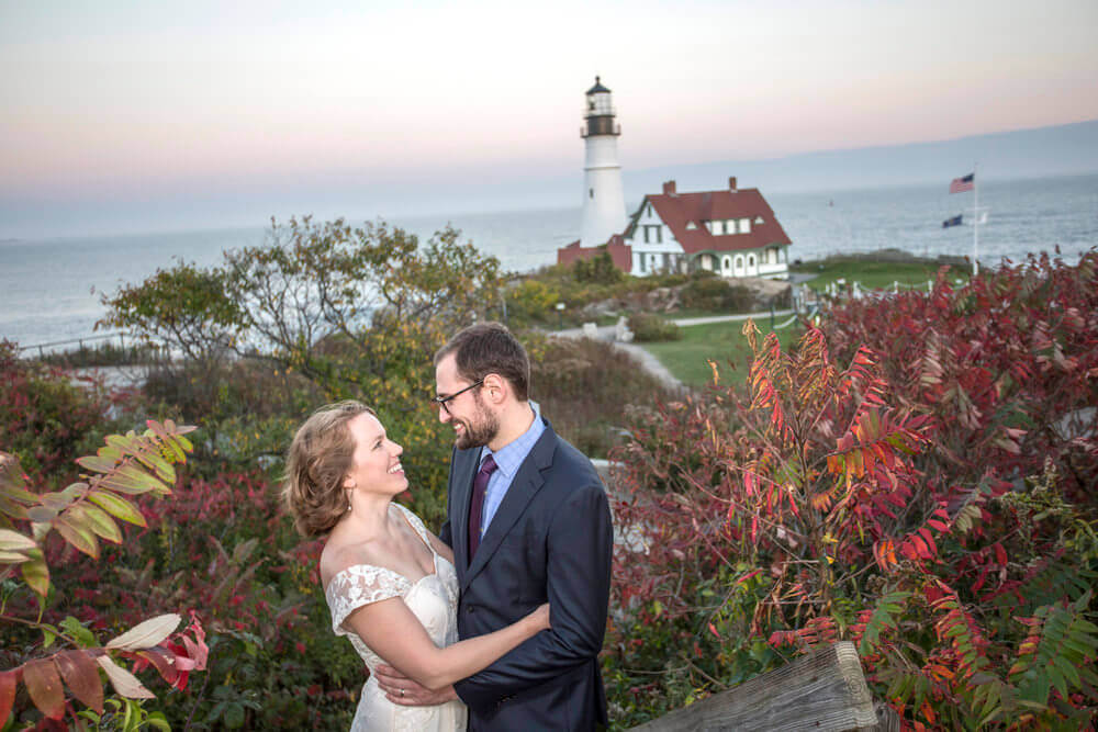 Wedding photography of a couple embracing at Portland Head Lighthouse in Cape Elizabeth Maine
