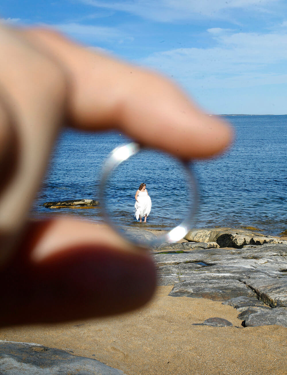Wedding photography of the bride in the ocean seen through the wedding ring held by the groom