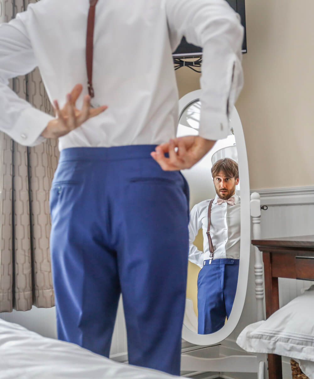 Wedding photography of the groom getting ready for the ceremony in his hotel room in Maine