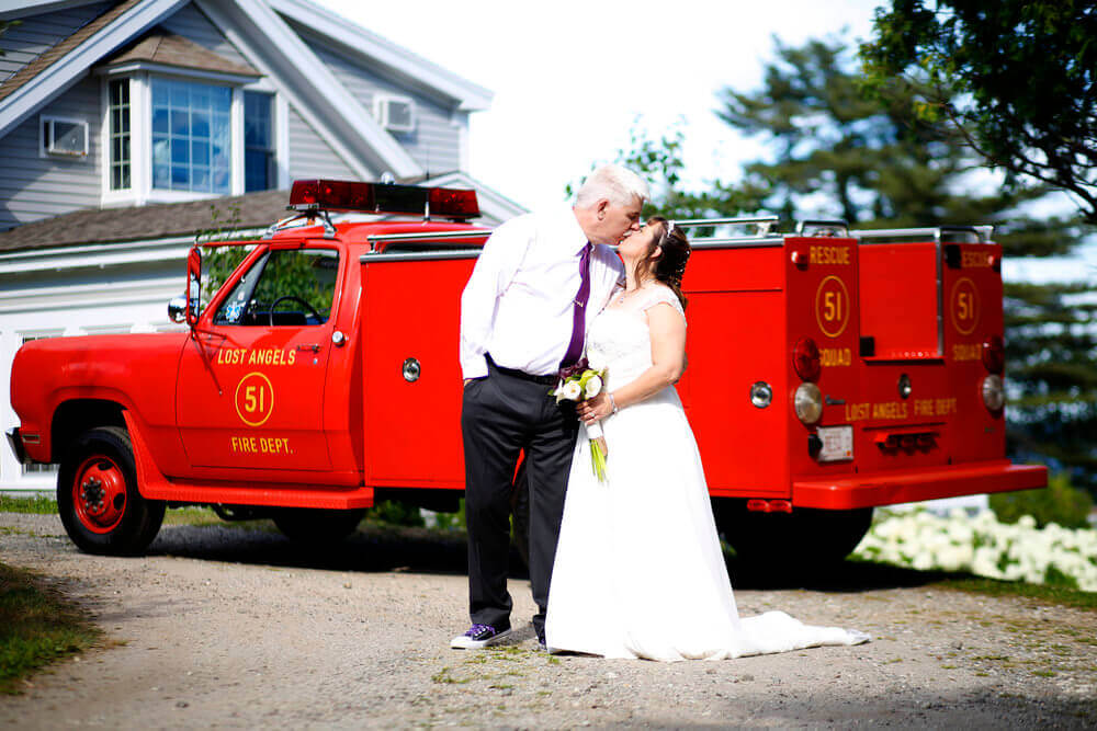 Wedding photography of a wedding couple kissing in front of an antique firetruck