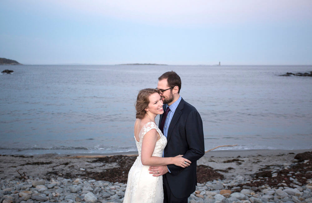 Wedding photography of the couple on the beach at Portland Head Lighthouse in Maine