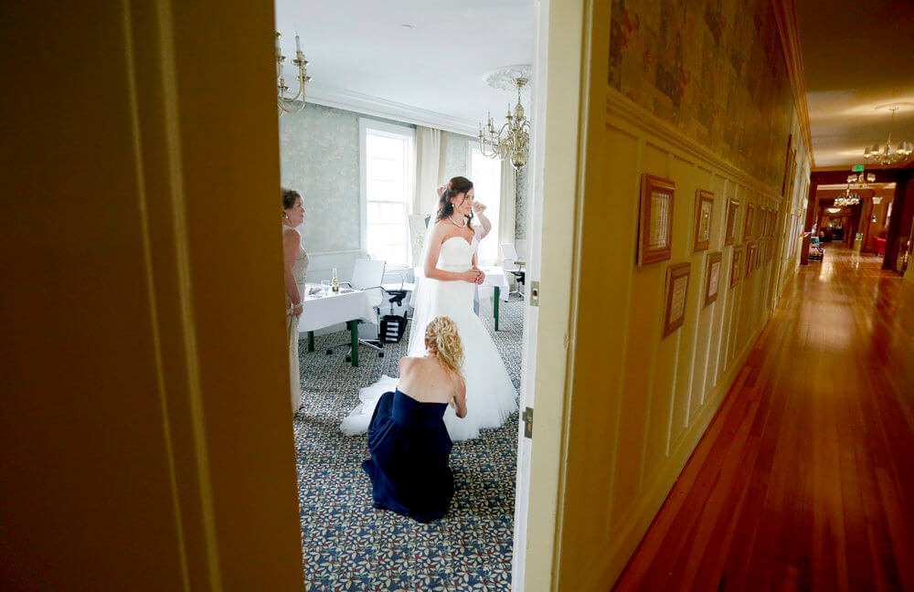 Wedding photography of a bride seen through the doorway getting ready for the ceremony in Maine