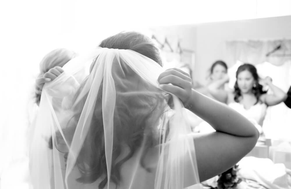 Wedding photography of a bride seen on a mirror adjusting her veil before the ceremony