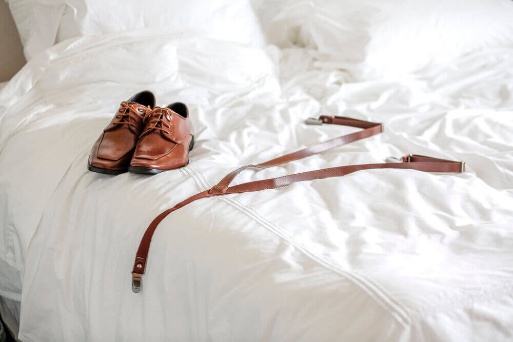 Wedding photography of the grooms shoes and suspenders on the bed