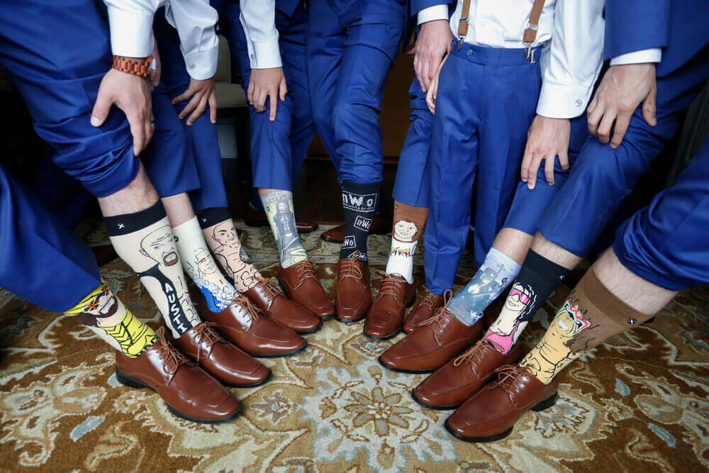 Wedding photography of the groomsmen showing off their wrestling themed socks in Kennebunk Maine