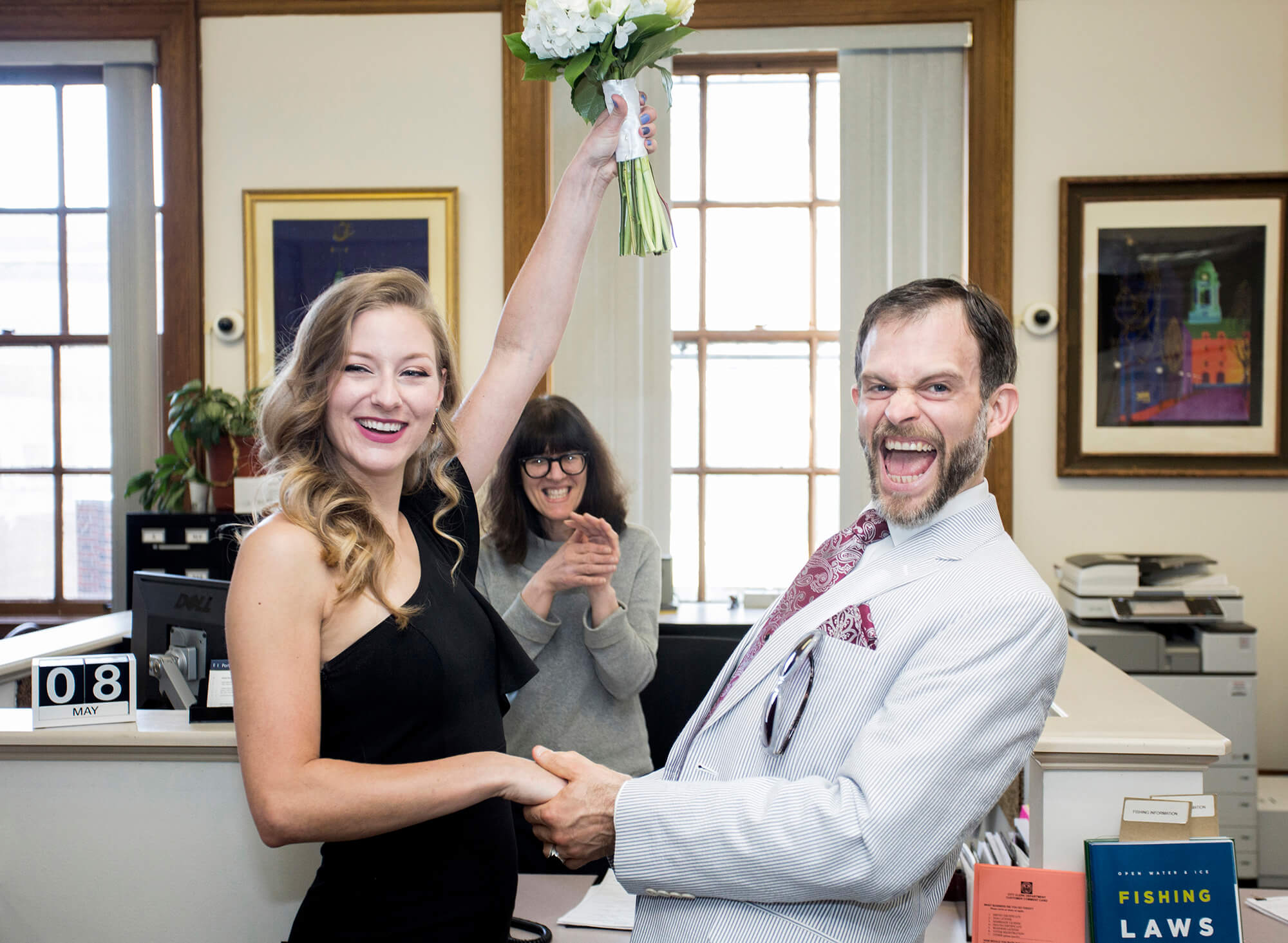 Wedding photography of a couple celebrating after signing their marriage paperwork at Portland City Hall