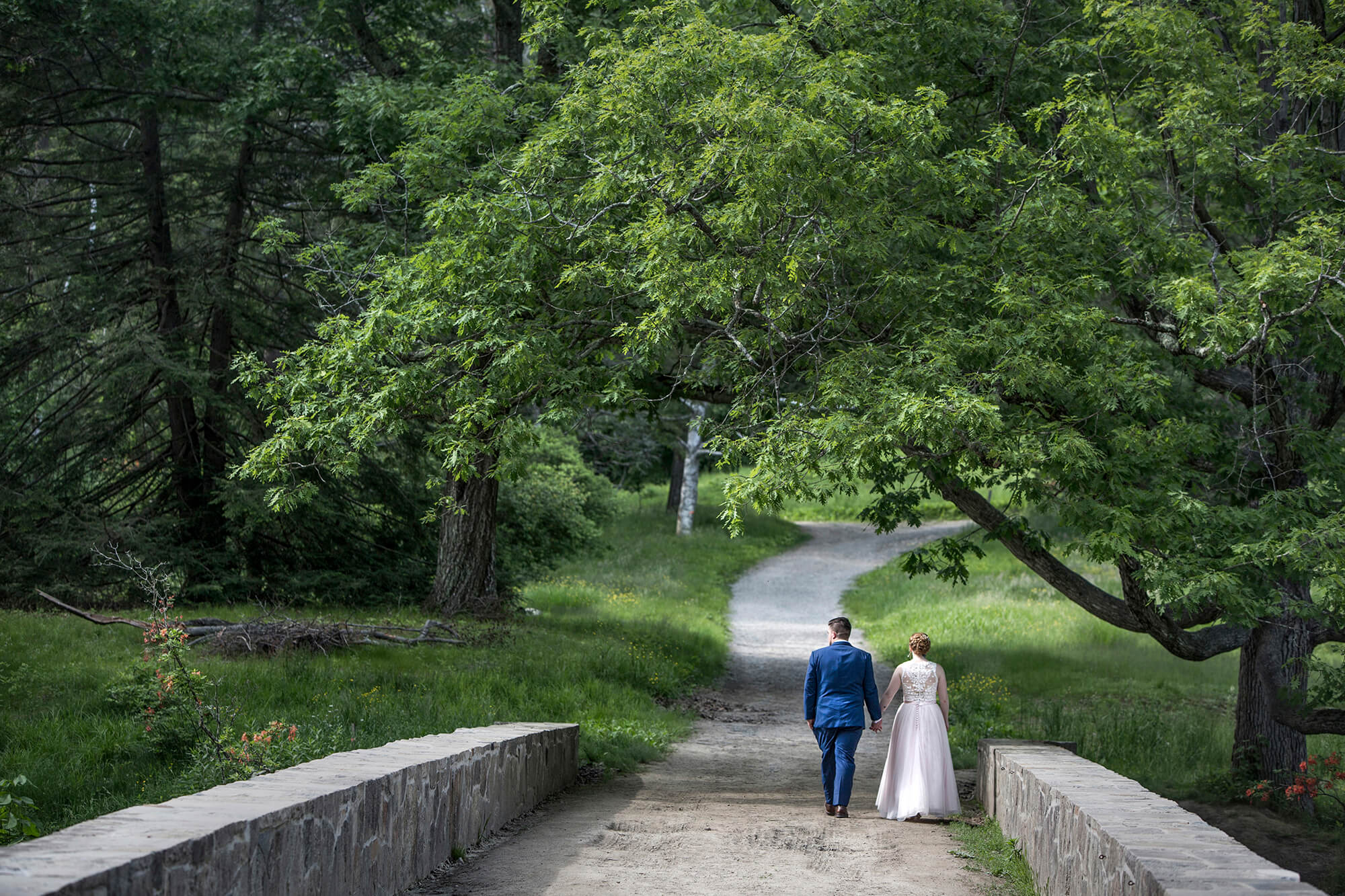 Wedding photography of a bride and groom holding hands walking away over a stone bridge