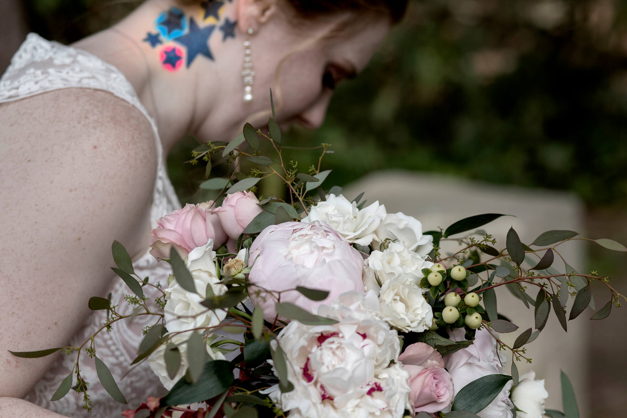 Wedding photography of the close-up of the bride's neck tattoo and flowers