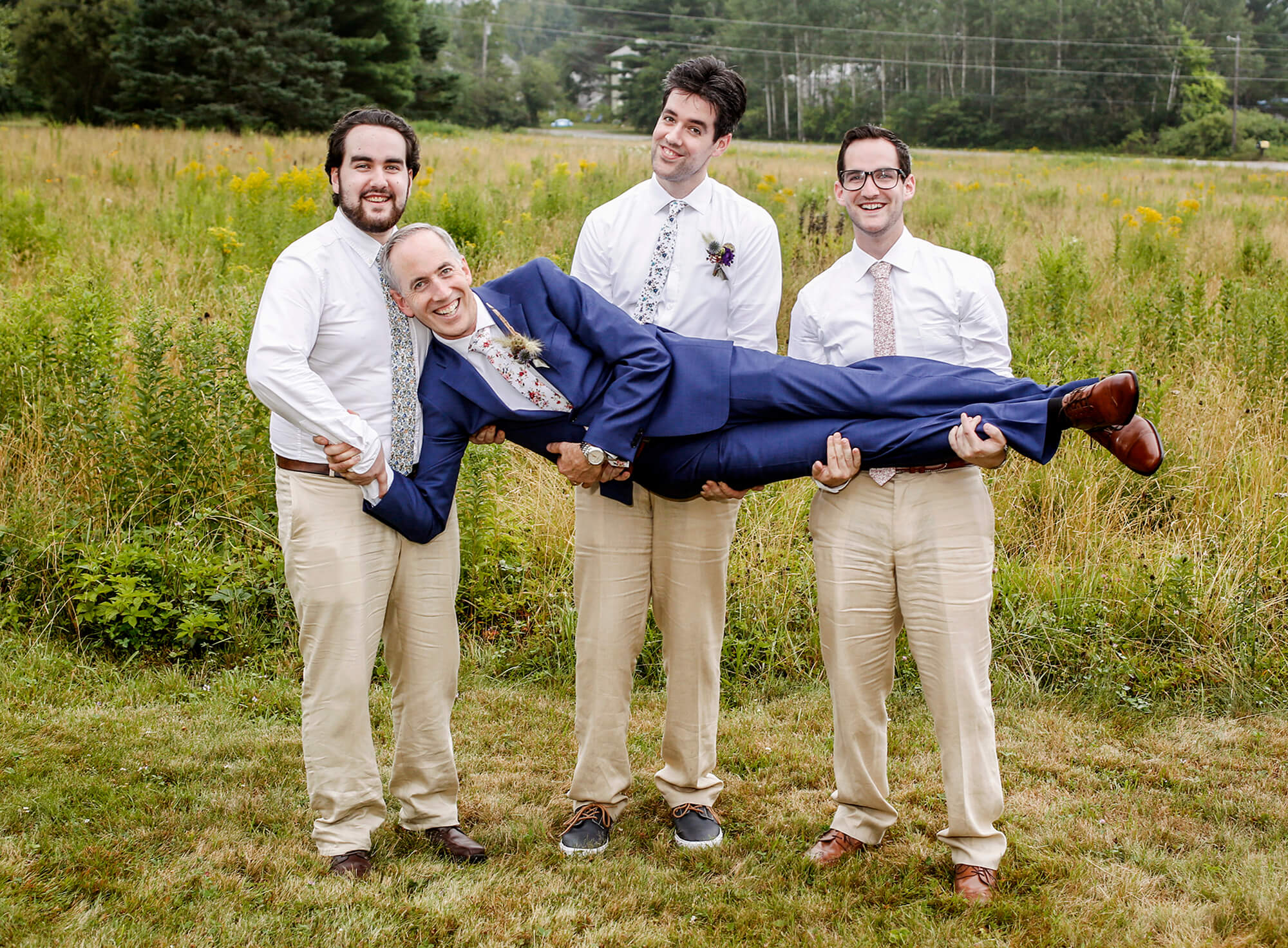 Wedding photography of three sons holding their father for a photo
