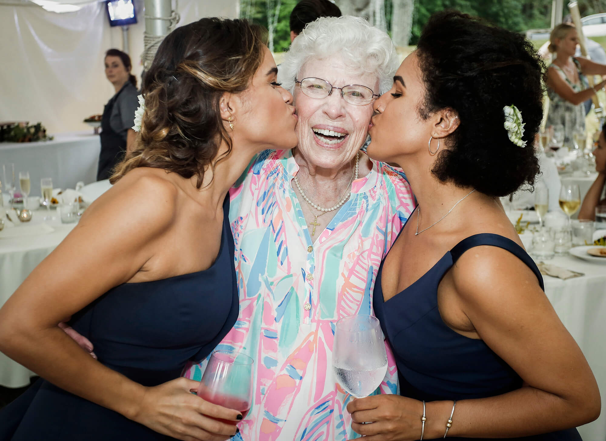 Wedding photography of two bridesmaids kissing their grandmother on each cheek during the reception