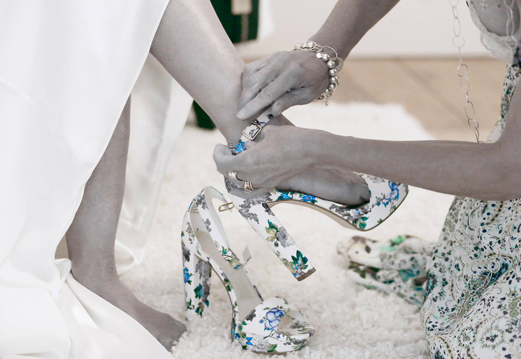 Wedding photography of a bride getting help putting on her shoes