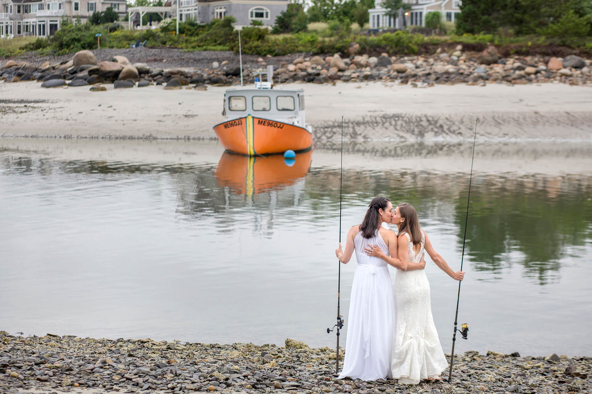 Wedding photography of couple kissing while holding fishing poles along the water