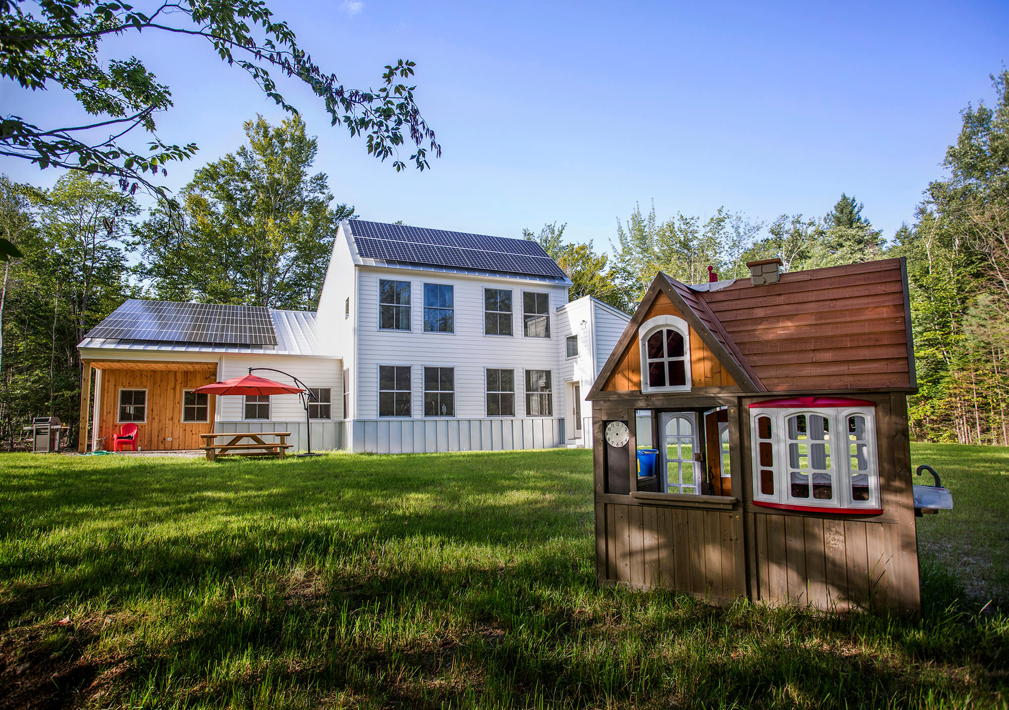 Architectural Photography, View of a play house and new green home in rural Maine