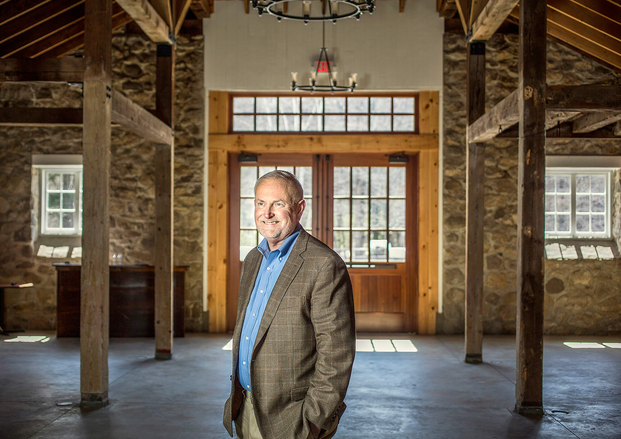 Portrait photography of Saint Joseph's College President Dr. James Dlugos in The Stone Barn at Sebago Lake on the Saint Joseph's College campus in Standish