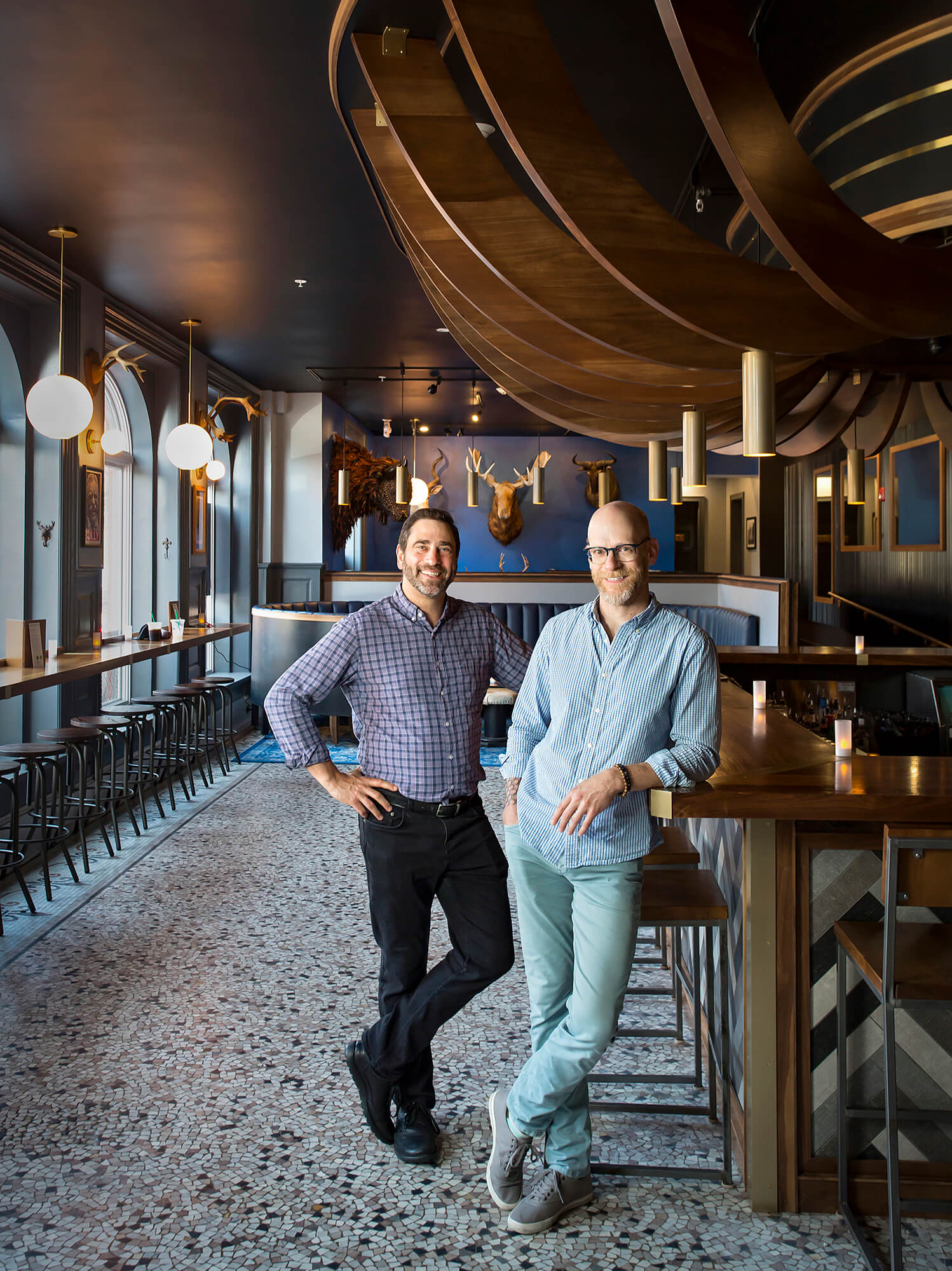 Portrait photography of Phil Kaplan, principal of Kaplan Thompson Architects, left, and Jamie Broadbent, architect and an associate with Kaplan Thompson Architects, in the Sagamore Hill Lounge in Portland