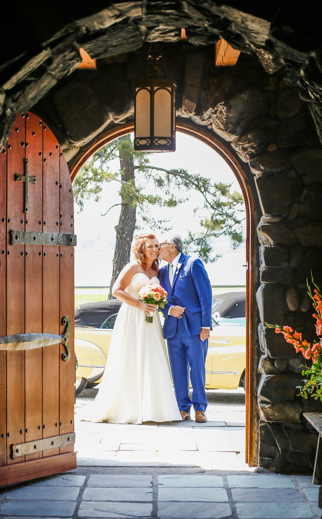Wedding photography of the father of the bride seen through the doorway of a church kissing his daughter the bride