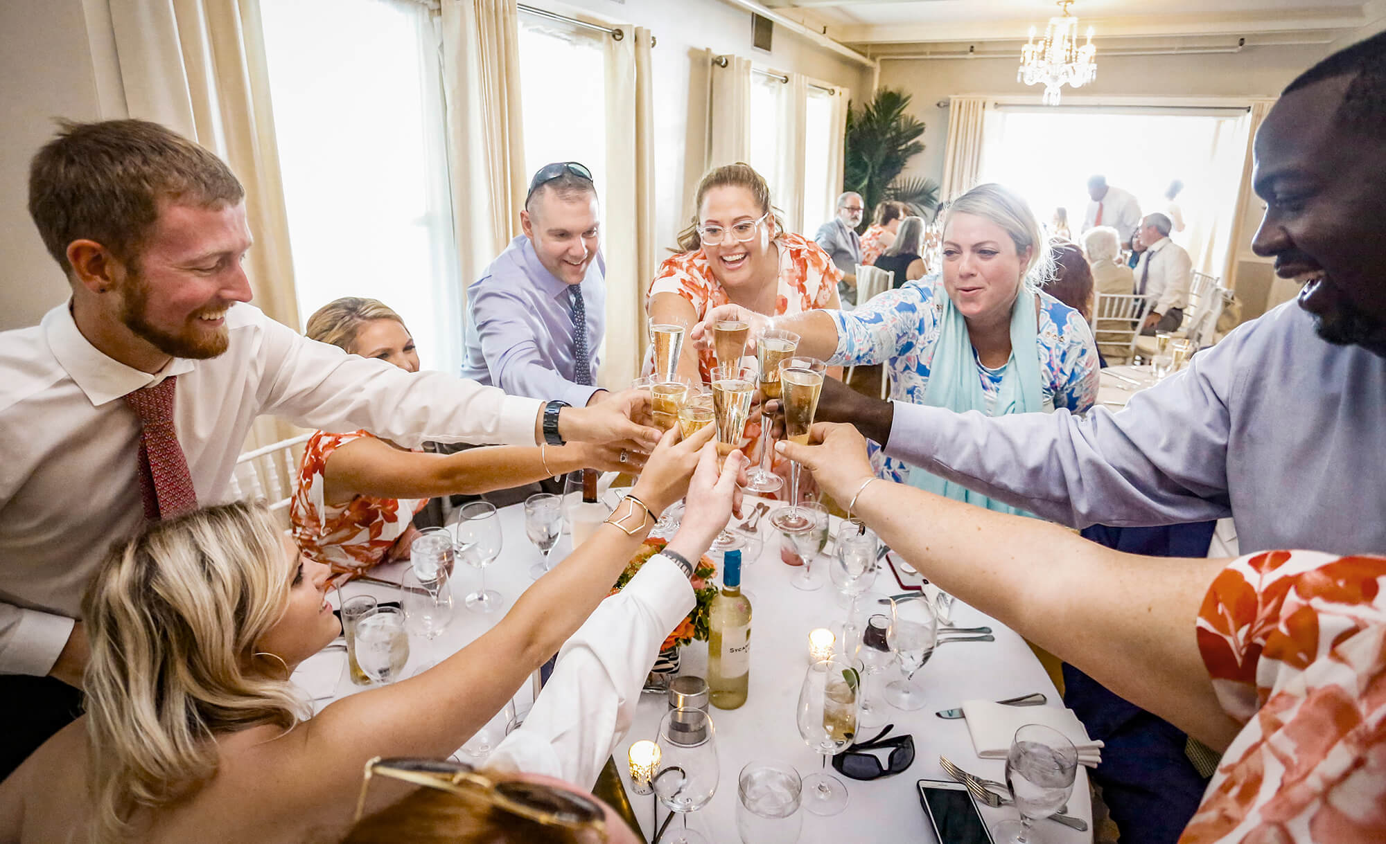 Wedding photography of people toasting the bride and groom in Maine