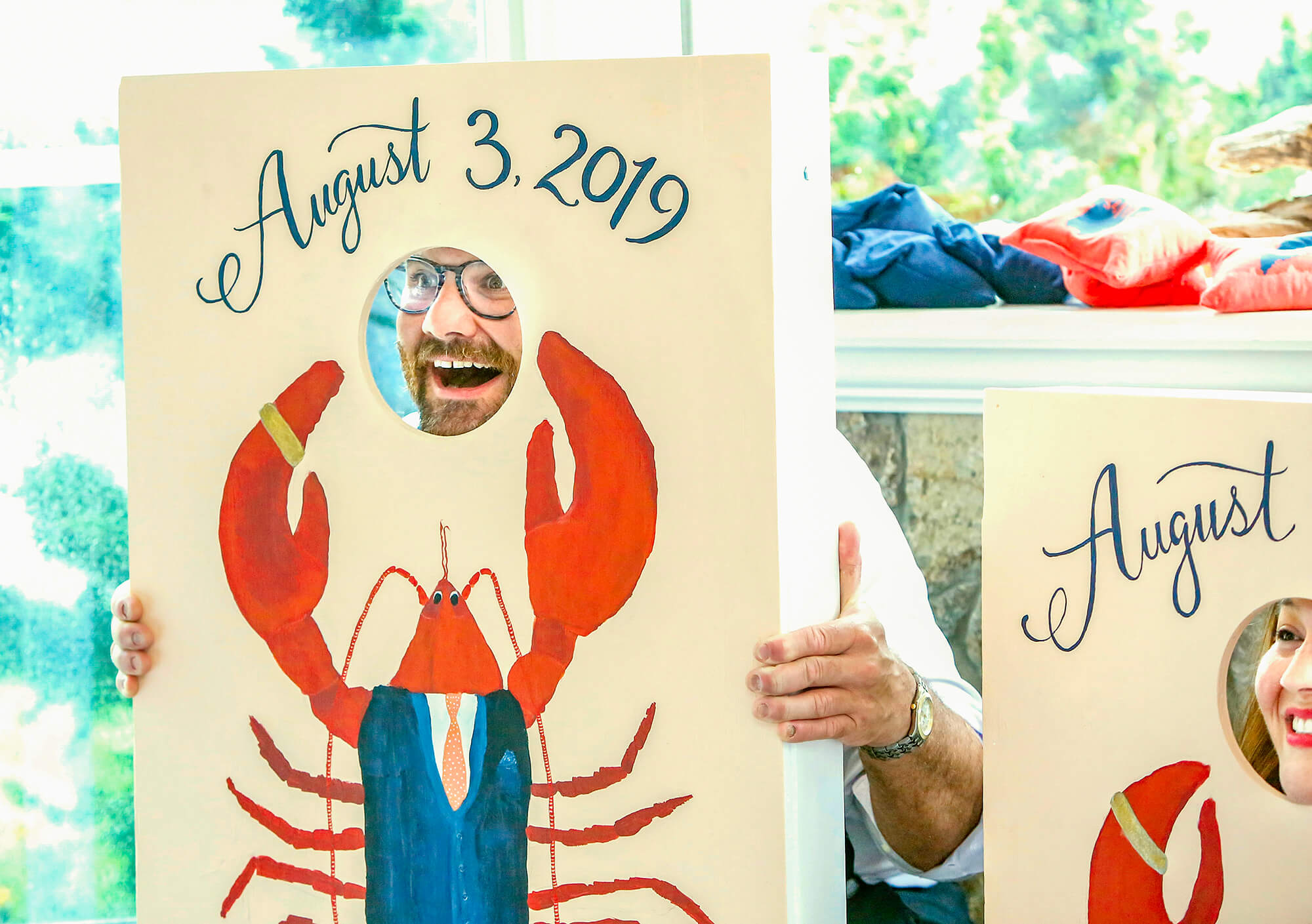 Wedding photography of guests looking through the opening of a lobster themed corn hole board