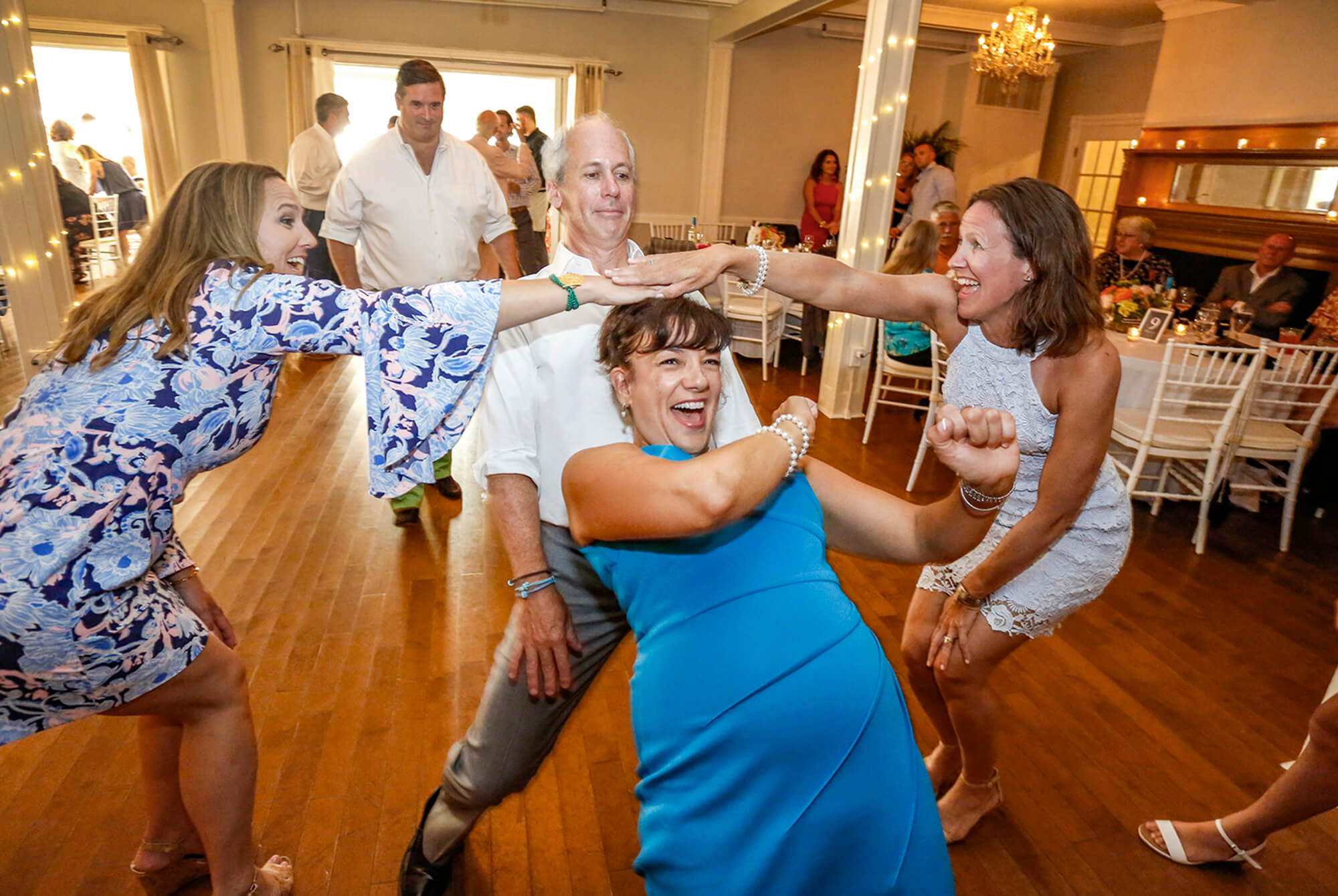 Wedding photography of a woman doing the limbo during a wedding reception in Maine