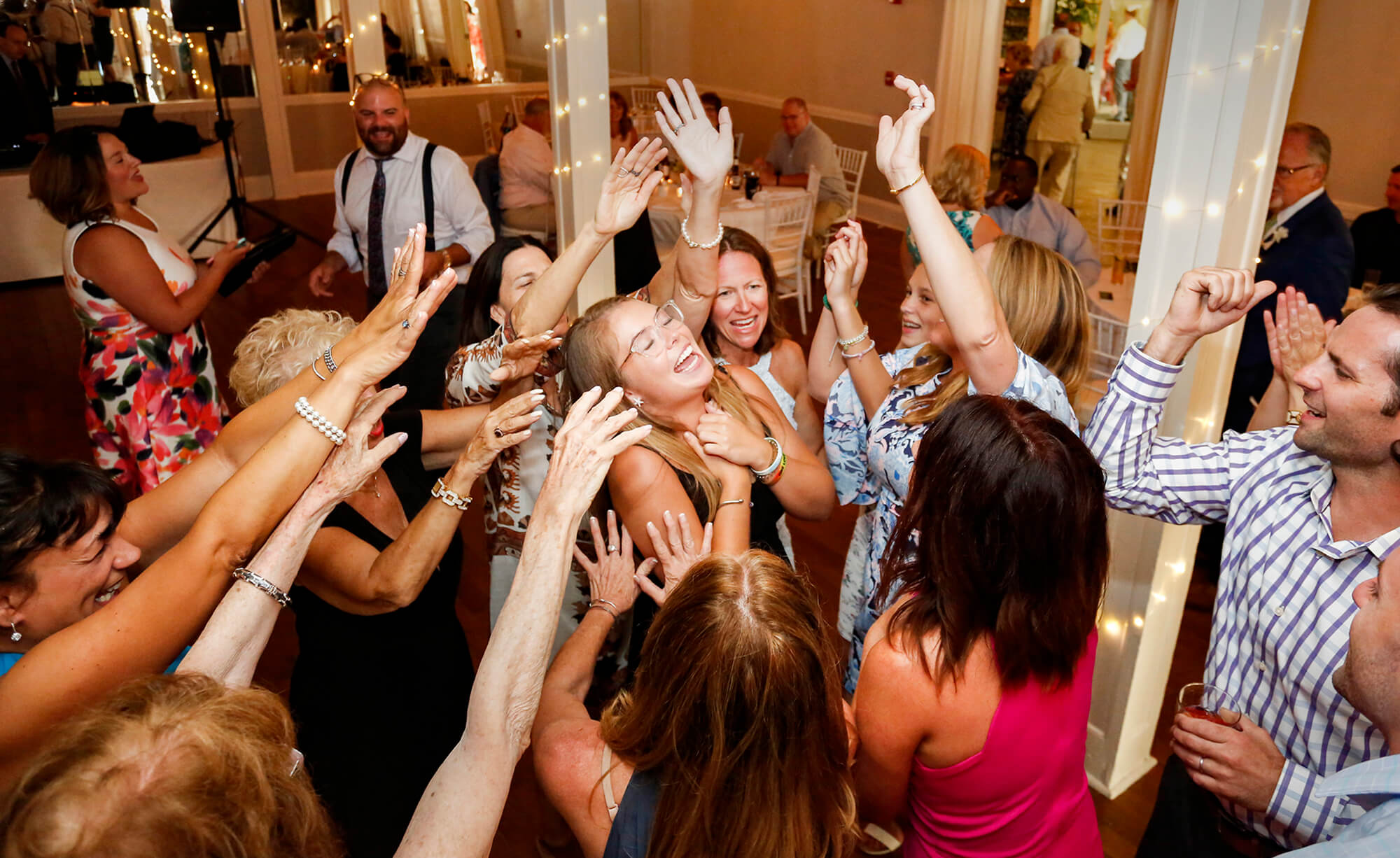 Wedding photography of people raising their hands around a girl dancing during the reception in Maine
