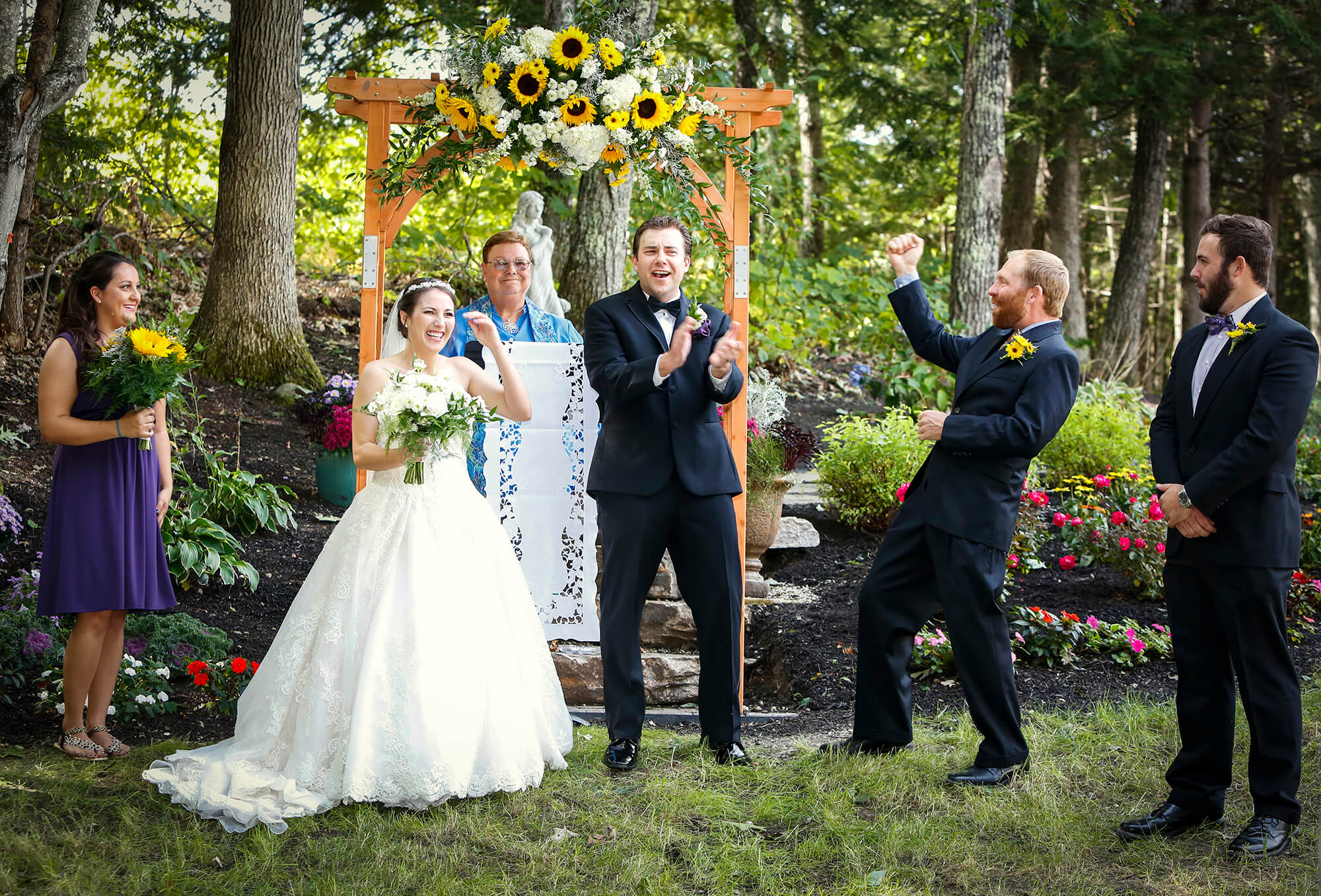 Wedding photography of the couple and bridal party celebrating during the ceremony