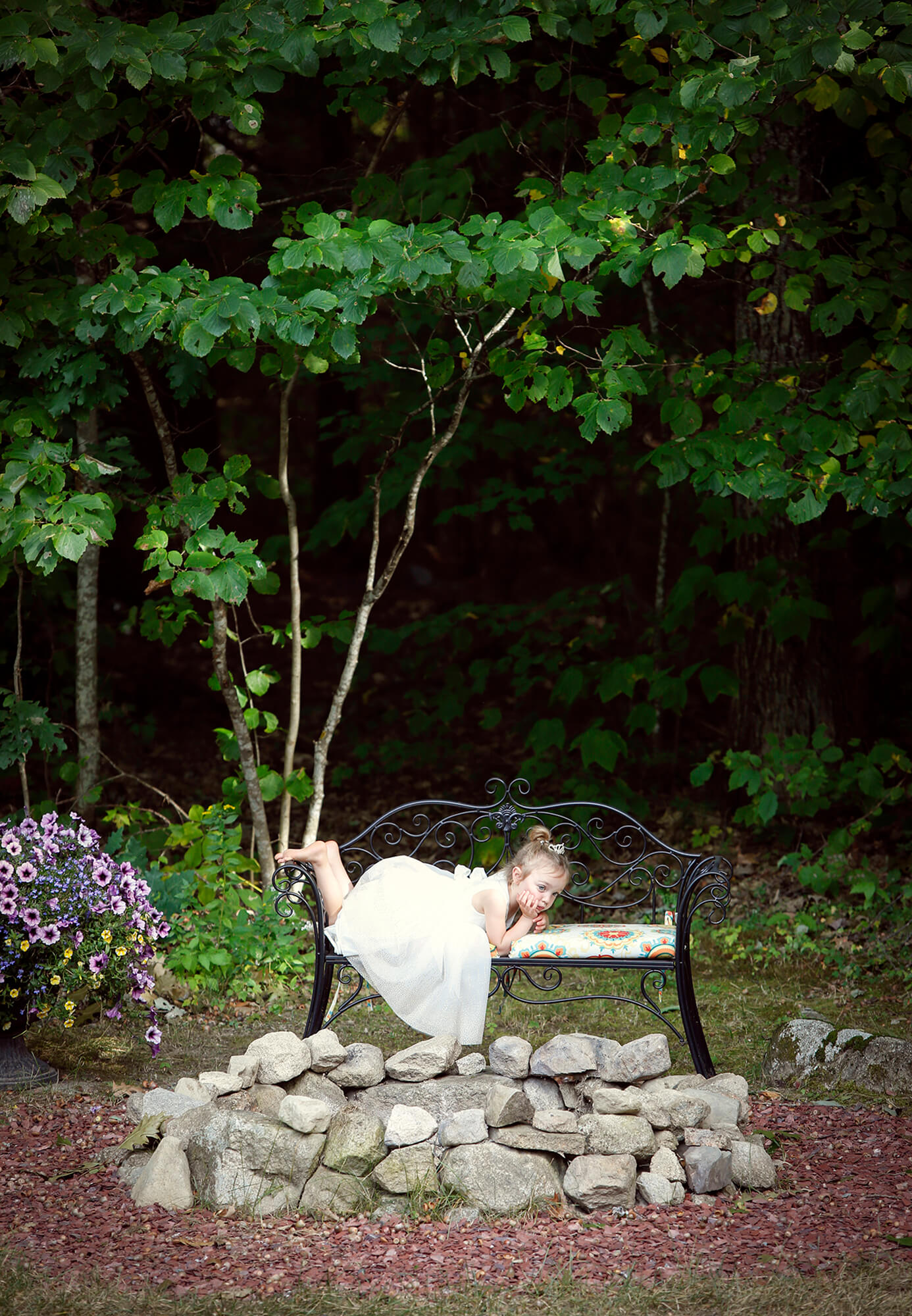 Wedding photography of a bored little girl laying on a bench during the reception