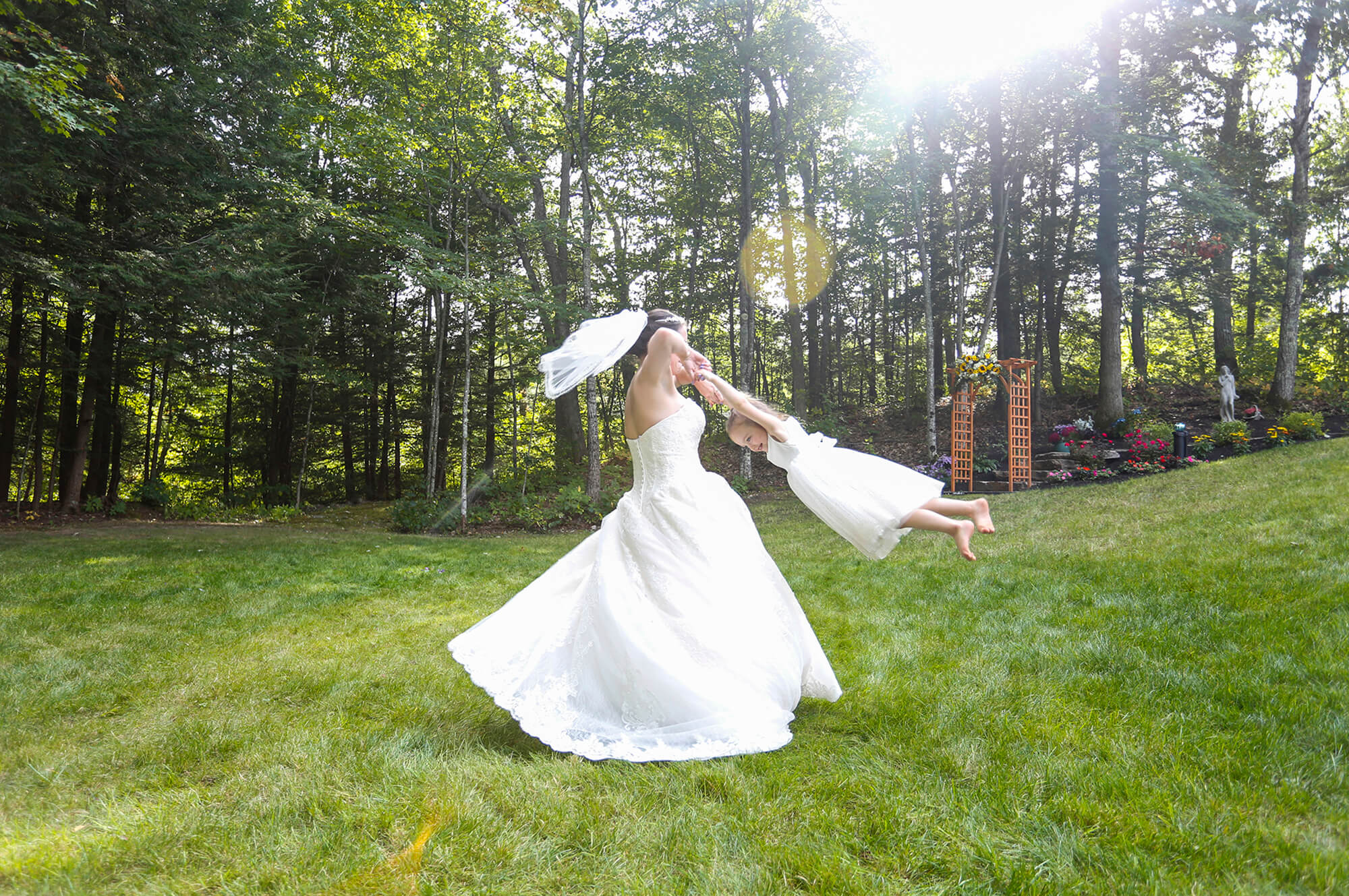 Wedding photography of bride twirling a little girl by the hands during the reception