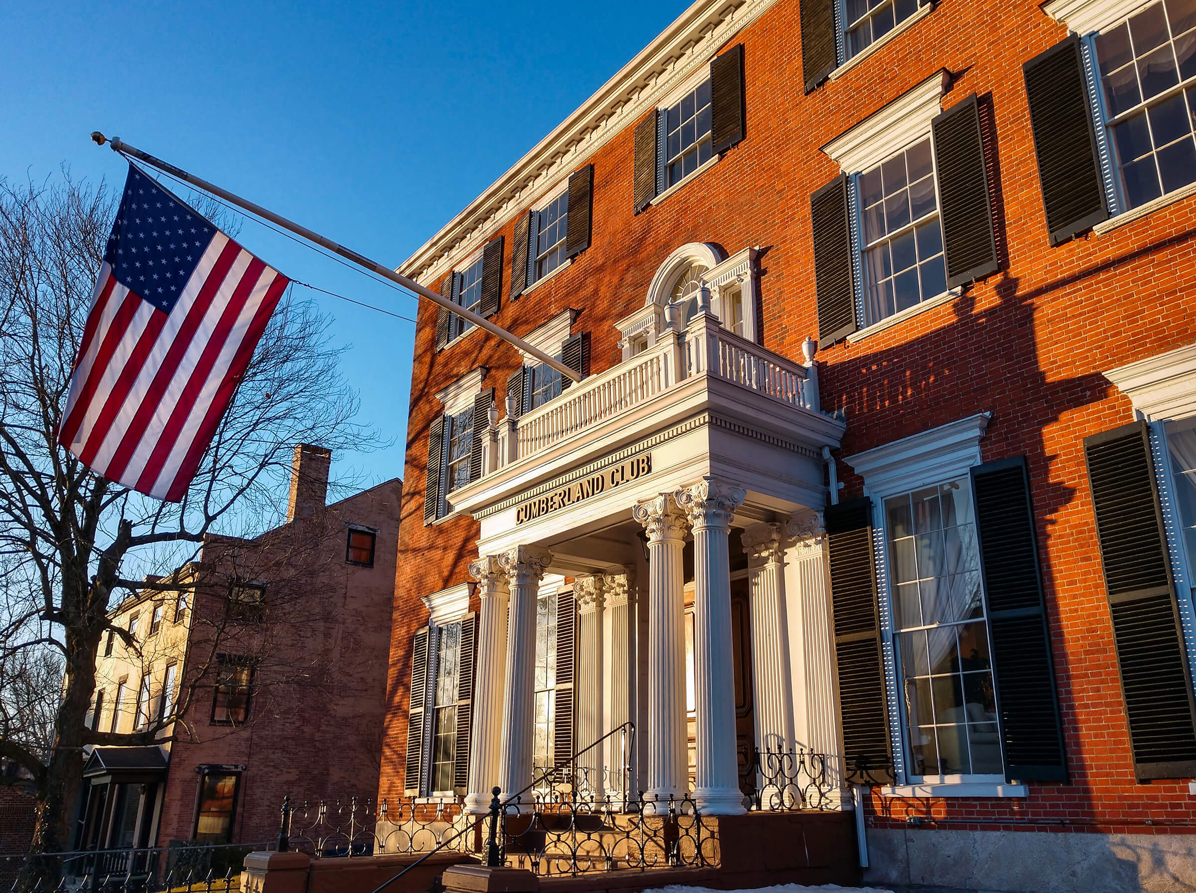 Architectural Photography of the Cumberland Club, American flag hangs on the outside in the early morning light in Portland, Maine