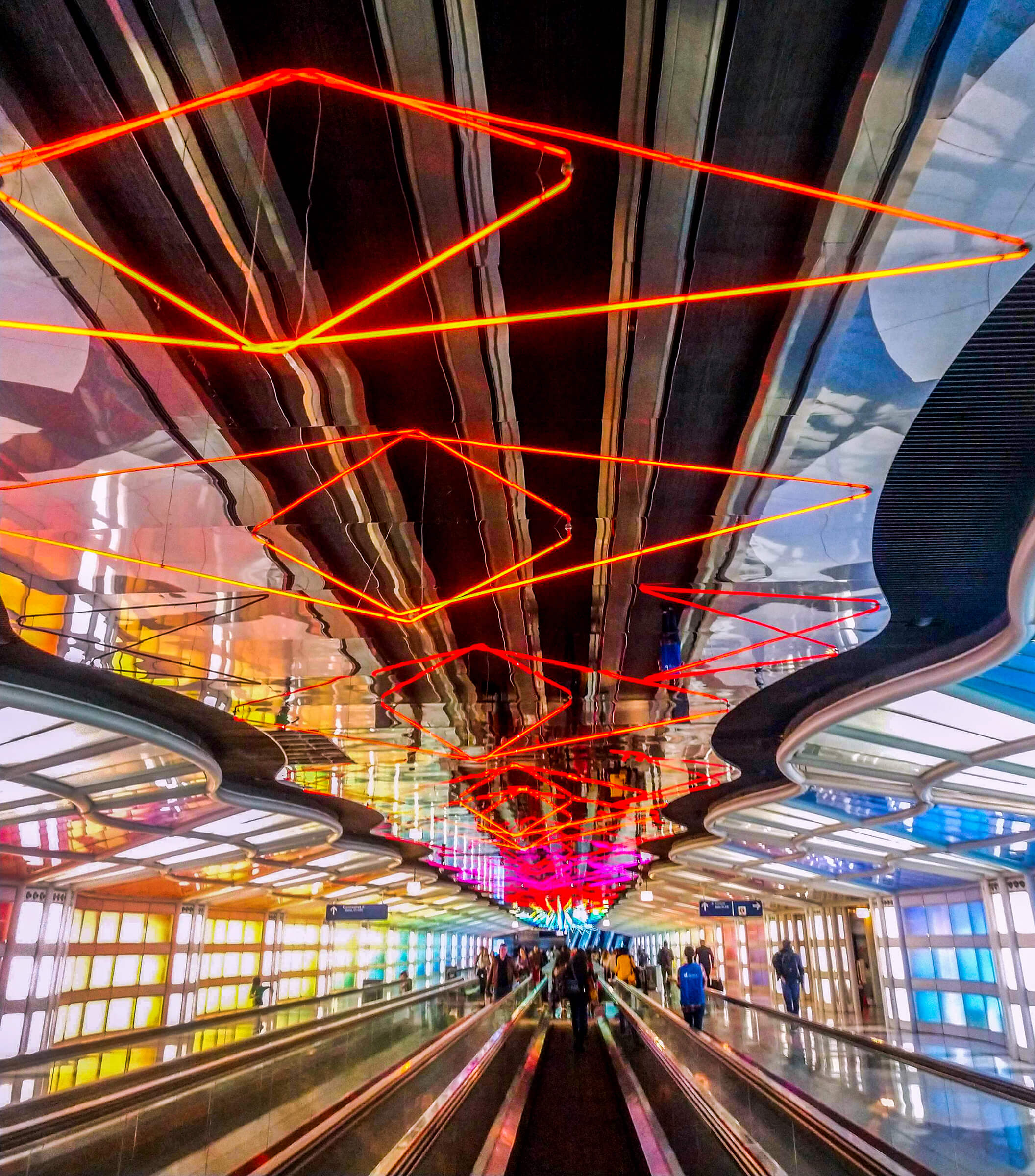 Architectural Photography Chicago O'Hare Airport, people walk on a escalator in a colorful terminal