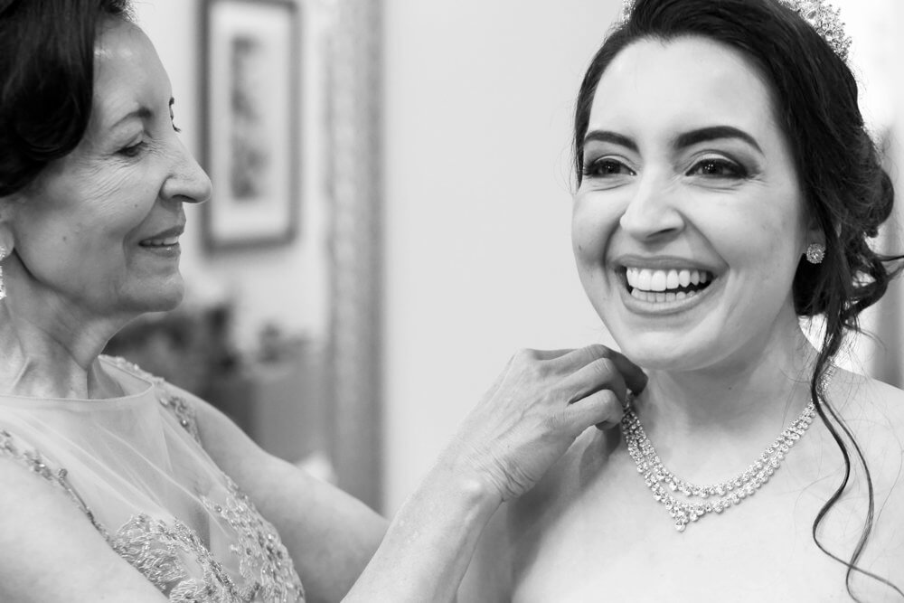 Wedding photography of the mother of the bride putting on the necklace of a smiling bride