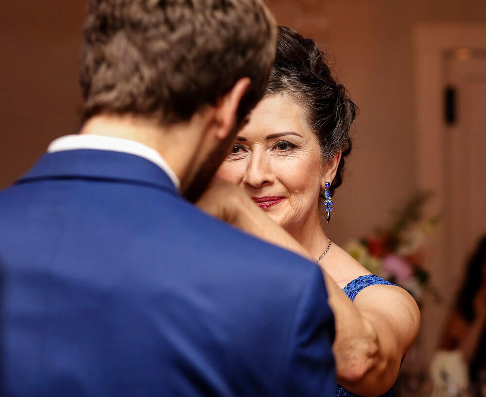 Wedding photography of a mother getting her hand kissed by her son during their dance